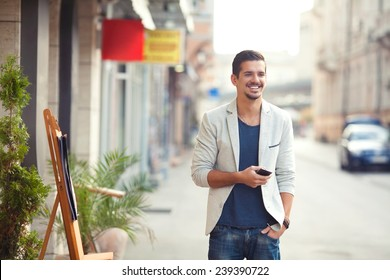 Handsome young man standing on the street holding mobile phone