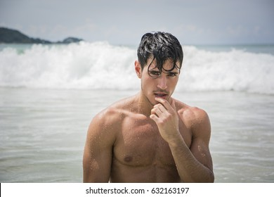 Handsome young man standing on a beach in Phuket Island, Thailand, shirtless wearing boxer shorts, showing muscular fit body