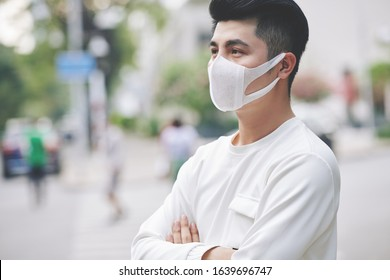 Handsome young man standing outdoors wearing medical mask to protect others from virus spread