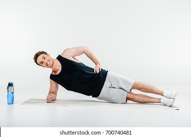 handsome young man standing side plank isolated on white