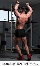 Handsome Young Man Standing Strong In The Gym And Flexing Muscles - Muscular Athletic Bodybuilder Fitness Model Posing After Exercises
