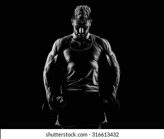 handsome young man in the studio with dumbbells on a dark background
