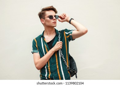 Handsome young man in a stylish beach shirt adjusts sunglasses on the beach near the green wall