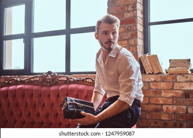 A handsome young man with a stylish beard and hair elegantly dressed holding a gift box while sitting on a red vintage sofa.