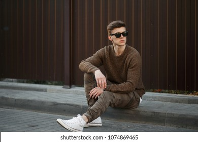 Handsome young man in stylish sunglasses with a pullover and military fashionable pants with white sneakers sits on the street near the metal wall