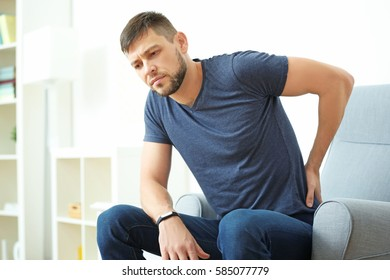 Handsome young man suffering from backache at home
