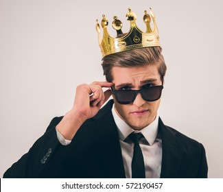Handsome young man in suit, crown and sun glasses is looking at camera while standing with crossed arms on gray background