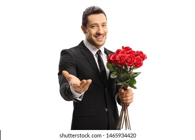Handsome young man in a suit holding a bunch of red roses and showing at the camera with his hand isolated on white background