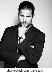 handsome young man in suit on grey background. Business man with wrist watch