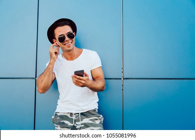 Handsome young man in sunglasses listening to music in headphones on his gadget. Dressed in stylish clothes, wearing black hat. Outdoors. Copy space