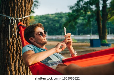 Handsome young man in sunglasses lying at sunset in a hammock and using a smartphone. The guy is resting in a hammock in the park in the evening.