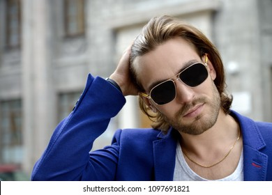 Handsome young man in sunglasses on a city street. Men's beauty, fashion. Active lifestyle.