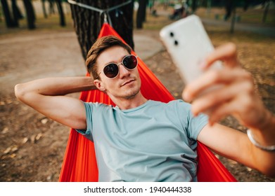 Handsome young man taking a selfie on a smartphone while lying on a red hammock in the woods on a tree, looking at the camera of a smartphone with a serious face. Rest in the park.