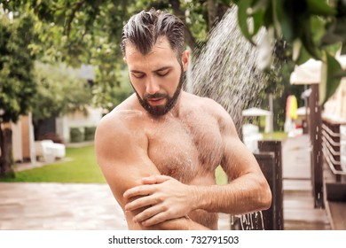 Handsome young man taking shower, outdoors