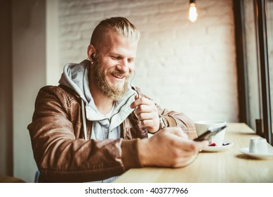 handsome young man talking on the phone in coffee shop