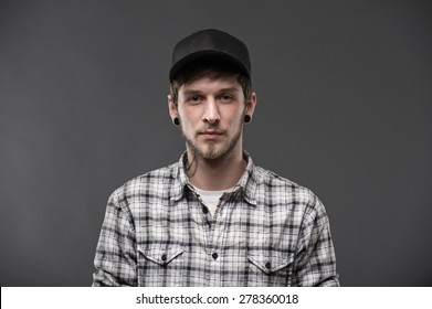 handsome young man with tattoo on the neck. in a plaid shirt and a baseball cap. looking directly at the camera seriously, isolated on black background
