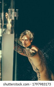 handsome young man in tattoos in the shower. lifestyle concept.