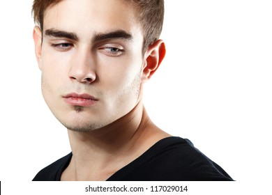 Handsome young man touching his hair, portrait of sexy guy looking down at corner over white background