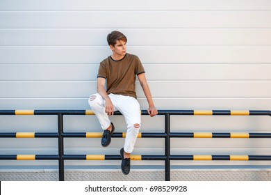 handsome young man in trendy stylish clothes sits near a glossy modern wall
