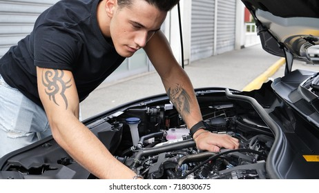 Handsome young man trying to repair a car engine, looking inside open bonnet