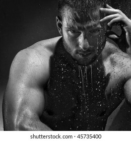 A Handsome young man under the shower dripping wet