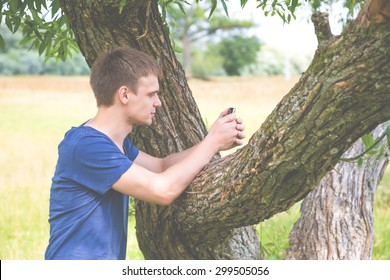 Handsome young man under the tree with your smartphone
