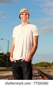 Handsome young man in a urban fashion pose along a railroad track.