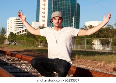 Handsome young man in an urban lifestyle pose along railroad tracks with his arms stretched out and wearing a baseball cap.