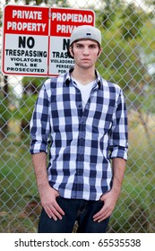 Handsome young man in an urban lifestyle fashion pose along a fenced lined sidewalk.