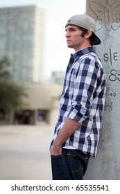 Handsome young man in an urban lifestyle fashion pose leaning against a utility pole wearing a baseball cap.