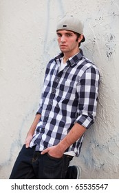 Handsome young man in an urban lifestyle fashion pose leaning against an alley wall.