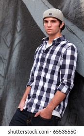 Handsome young man in an urban lifestyle fashion pose leaning against a graffiti wall.