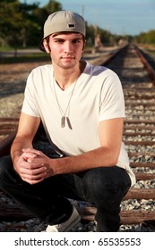 Handsome young man in an urban lifestyle fashion pose kneeling on a railroad track.