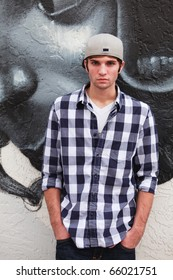 Handsome young man in an urban lifestyle fashion pose leaning against a graffiti wall wearing a baseball cap.