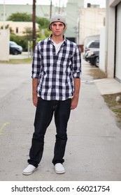 Handsome young man in an urban lifestyle fashion pose standing in a downtown alley wearing a baseball cap.