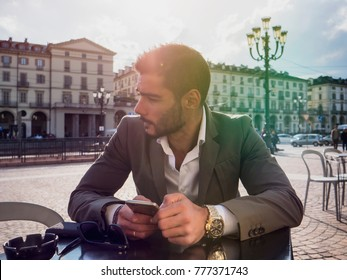 Handsome young man using cellphone, wearing elegant coat posing at bar table outside on urban background.