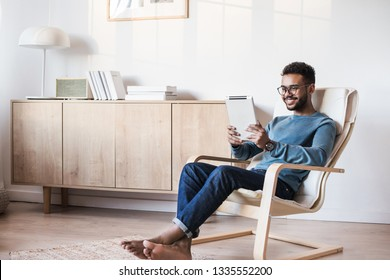 Handsome young man using digital tablet at home. Student men resting in his room. Home work or study, freelance concept