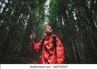 Handsome young man using his mobile phone to find his location in the mountain woods, he is looking for connection to the internet. Guy wearing a red rain jacket and rucksack.