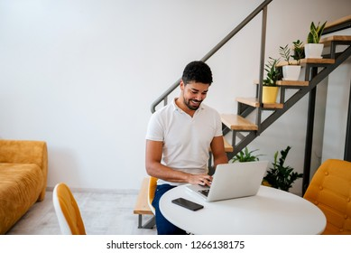 Handsome young man using laptop at modern cozy home.