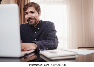 Handsome young man using laptop computer at home. Student men in his room. Online shopping, home work, freelance, online learning, studying concept. Distance education