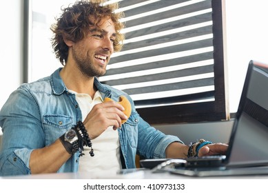 Handsome young man using laptop while to have lunch at restaurant bar.