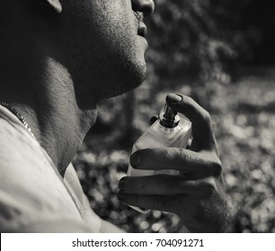 Handsome young man using perfume on green background