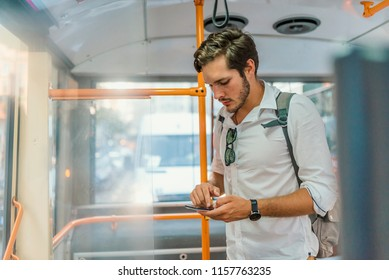 Handsome young man using smartphone in bus.  Handsome man standing in city bus and typing a message on the phone. Businessman commuting to work by bus and working with a smartphone