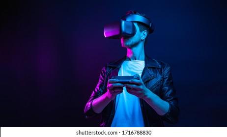 Schöner junger Mann mit einem Headset für virtuelle Realität auf dunkelbraunem, buntem Hintergrund