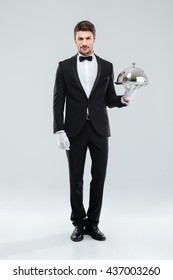 Handsome young man waiter standing and holding tray and lid over white background