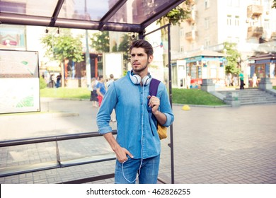 handsome young man  waiting his bus at bus stop