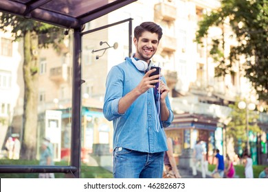 handsome young man  waiting his bus and smiling