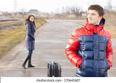 Handsome young man waiting in the road with a suitcase standing patiently with his hands in his pockets while a yong woman walks by behind him