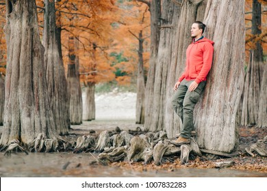 Handsome young man walking in autumn park among cypresses trees.