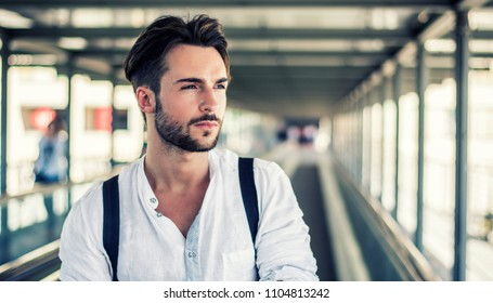 Handsome young man walking in city with backpack on shoulders, wearing white shirt